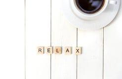 Les mots de détendent rassemblé en mots croisé avec la tasse de café sur les cubes en bois Image libre de droits