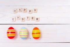 Les mots de Joyeuses Pâques sont écrits sur les cubes et les oeufs en bois Concept heureux de Pâques sur le fond en bois blanc Images libres de droits