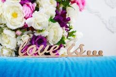 Les mots en bois AMOUR EST dans la perspective d'un bouquet fleurit Image libre de droits