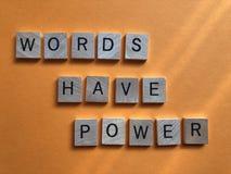 Les mots ont la puissance, d'isolement sur le fond orange photo stock
