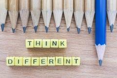 Les mots pensent différent sur la table en bois avec le groupe de crayons Image stock