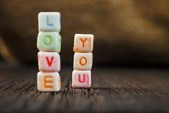 Les mots vous aiment écrit dans les blocs en céramique sur le fond en bois brun Photographie stock