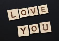 Les mots VOUS AIMENT sur en bois signe plus de le noir Photographie stock