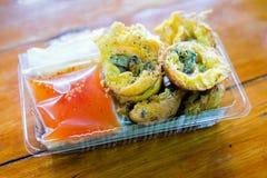 Les moules dans des boules de Takoyaki servent sur la boîte en plastique avec de la sauce douce Photo stock