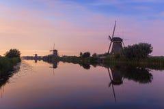 Les moulins à vent chez Kinderdijk ont silhouetté contre le ciel néerlandais de soirée Images stock