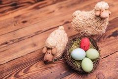 Les moutons de jouet de Pâques s'approchent du panier d'oeufs Photos libres de droits