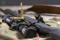 Les munitions avec le fusil noir d'action de boulon et portée sur le fond de multicam Fin vers le haut photos stock