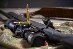 Les munitions avec le fusil noir d'action de boulon et portée sur le fond de multicam Fin vers le haut images libres de droits