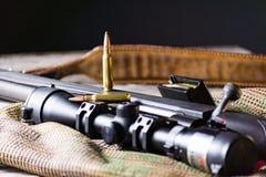 Les munitions avec le fusil noir d'action de boulon et portée sur le fond de multicam Fin vers le haut image stock