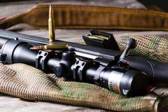 Les munitions avec le fusil noir d'action de boulon et portée sur le fond de multicam Fin vers le haut photographie stock