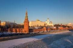 Les murs rouges du coucher du soleil Kremlin à Moscou près ont glacé la rivière en hiver Images libres de droits