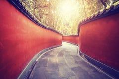 Les murs rouges sinueux passent entouré par la forêt en bambou Photo stock