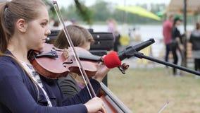 Les musiciens de rue gagnent l'argent liquide jouant sur le violoncelle et le violon, artistes exécutent la composition musicale  banque de vidéos