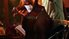 Les musiciens jouent dans une barre de jazz, dans le premier plan un homme avec une contrebasse banque de vidéos