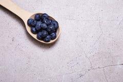 Les myrtilles organiques naturelles mûres juteuses de baies de cuillère en bois suivent un régime Photos libres de droits