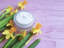 Les narcisses de jonquilles masquent la crème organique faite main de pot cosmétique un extrait en bois rose photo stock