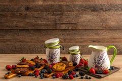 Les navires en céramique ont assorti avec les biscuits de chocolat et les fruits cuits au four de forêt sur le fond en bois photo libre de droits