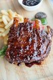 Les nervures de BBQ de porc, les nervures de viande ont étouffé avec de la sauce à BBQ Photographie stock