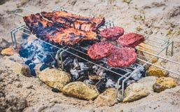 Les nervures de porc et les hamburgers sur le barbecue improvisé fait maison de BBQ grillent Photo stock