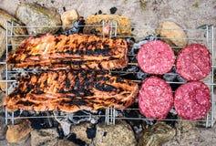 Les nervures de porc et les hamburgers sur le barbecue improvisé fait maison de BBQ grillent Photos stock