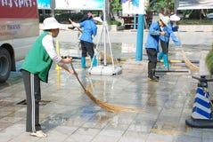 Les nettoyeurs balayent la rue image libre de droits