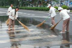 Les nettoyeurs chinois balayent la rue photo libre de droits
