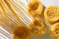 Les nids de spaghetti et de pâtes se tiennent droits sur une cuisine illuminée Photo stock
