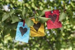 Les notes de papier bleues, jaunes et rouges avec le coeur forme Photographie stock libre de droits