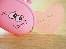 Les notes de papier collantes, vous aiment le mot, bourse rose avec le visage de sourire Images libres de droits
