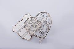 Les notes musicales sur un papier brûlé sous un coeur forment l'icône Photos stock