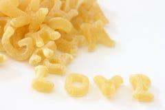 Les nouilles de pâtes dans l'alphabet donne la forme de l'amour de mot Photos stock