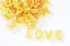 Les nouilles de pâtes dans l'alphabet donne la forme de l'amour de mot Photographie stock