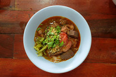 Les nouilles de riz se mélangent à de la sauce épicée à porc et les légumes servent dans la cuvette bleue Image stock