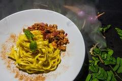 Les nouilles jaunes ont fait frire le porc haché épicé du plat blanc à l'arrière-plan Nourriture thaïe traditionnelle Photographie stock