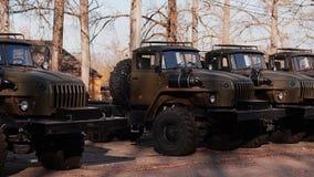Les nouveaux camions militaires sont dans une rangée sur le site Équipement d'armée clips vidéos