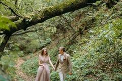 Les nouveaux mariés élégants marchent sur une traînée dans un bel endroit romantique sur la nature Cérémonie de mariage à l'extér photographie stock