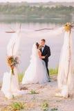 Les nouveaux mariés étreignants derrière la voûte décorée près de la rivière Photos libres de droits