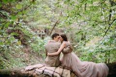 Les nouveaux mariés étreignent tendrement sur un plaid dans la forêt que les jeunes mariés se reposent sur la nature d'identifiez Images libres de droits