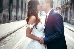 Les nouveaux mariés avec du charme tiennent des mains et les embrassent pendant le susent Portrait extérieur sensible Image stock