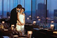 Les nouveaux mariés d'une manière de famille se tiennent dans un café vide le soir Photographie stock