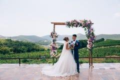 Les nouveaux mariés dans l'amour regardent l'un l'autre et apprécient le jour du mariage Ils se tiennent sur une voûte des fleurs Images libres de droits