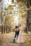 Les nouveaux mariés de Smilng étreignent sous une chute des feuilles d'automne image libre de droits