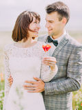 Les nouveaux mariés de sourire tiennent le pavot La verticale de plan rapproché Images stock
