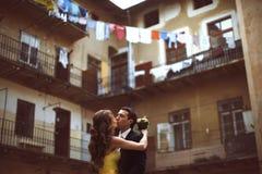 Les nouveaux mariés embrassent dans l'avant de la vieille maison avec des balcons Photographie stock libre de droits