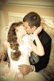 Les nouveaux mariés embrassent dans le palais de mariage Photos libres de droits