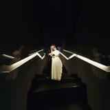 Les nouveaux mariés embrassent la position sur les escaliers illuminés avec le ligh au néon Photographie stock libre de droits