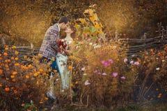 Les nouveaux mariés embrassent parmi les fleurs Image stock