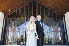 Les nouveaux mariés embrassent sous un voile sur le saule de fond Photos stock