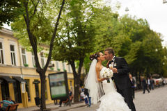 Les nouveaux mariés embrassent sur la rue de marche photos stock