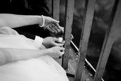 Les nouveaux mariés fixent la serrure sur le pont Photos stock